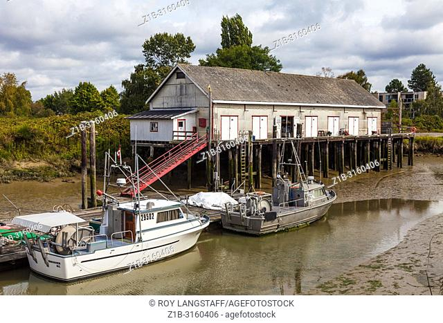 Commercial fishing boats docked in Scotch Slough at low tide in Steveston, British Columbia
