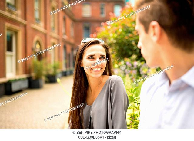 Young businesswoman and man talking outside office, London, UK