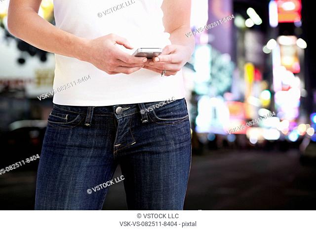 USA, Illinois, Metamora, Midsection of woman text-messaging in street at night