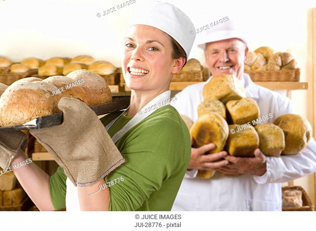 Bakers carrying loaves of fresh bread in bakery