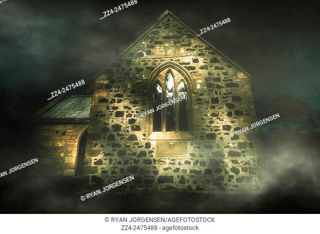 Artistic architecture photo of a spooky stone church in a haunted winters night