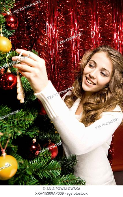young woman putting ornament on christmas tree
