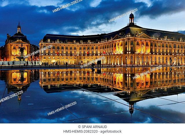 France, Gironde, Bordeaux, area listed as World Heritage by UNESCO, Bourse Place, La Lune harbour, night view of a historic building and its reflection on water...