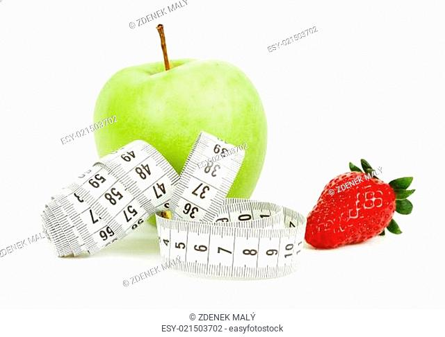 Measuring tape wrapped around a green apple and strawberry as a symbol of diet