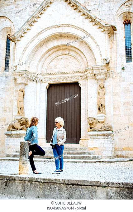 Two mature female friends chatting in front of historic building, Tuscany, Italy