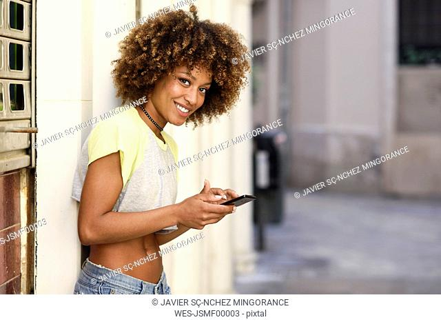 Portrait of smiling woman with afro hairstyle using smartphone outdoors