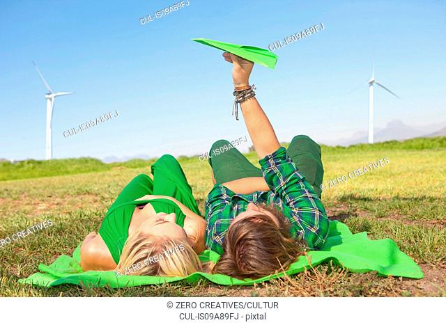 Young couple lying in field, man holding paper aeroplane