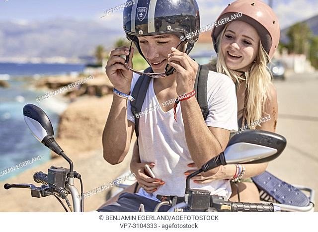Greece, Crete, Chersonissos, couple driving quad next to coast, man putting sunglasses on, eye protection, playful, teasing, relationship