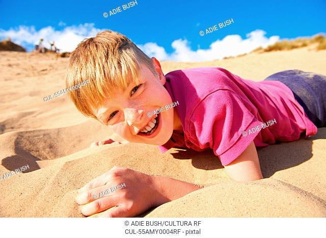 Blonde haired boy lying on beach