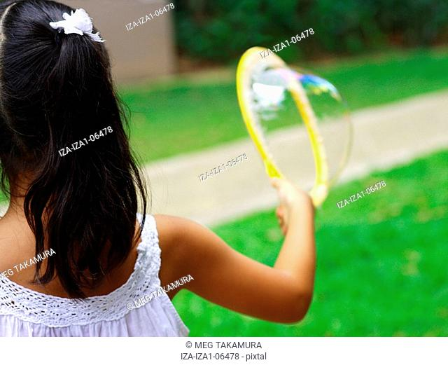 Rear view of a girl making a soap bubble