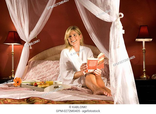 Woman having breakfast in canopy bed reading a book