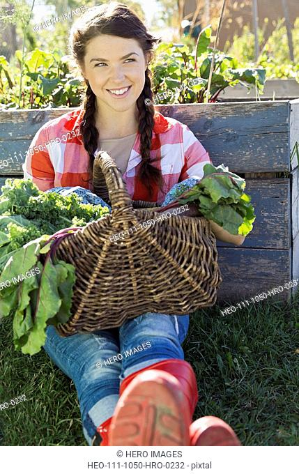 Woman sitting with vegetable basket in community garden