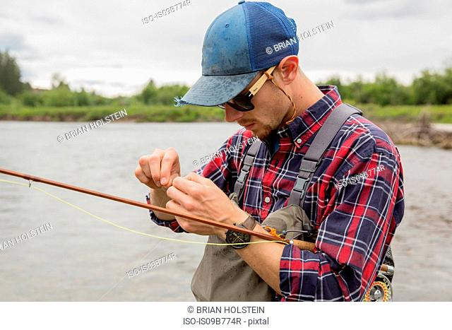 Man preparing bait in river, Clark Fork, Montana and Idaho, US