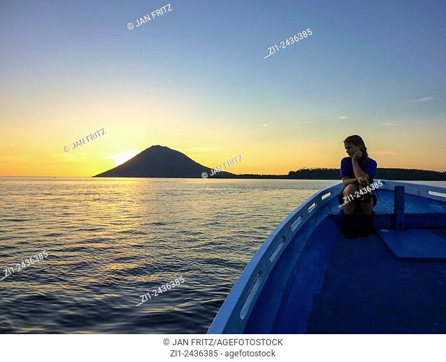 Gril at boat looking at volcano Manado Tua at sunset in Manado, Sulawesi, Indonesia