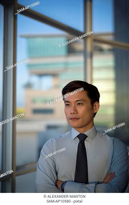 Singapore, Businessman standing at window
