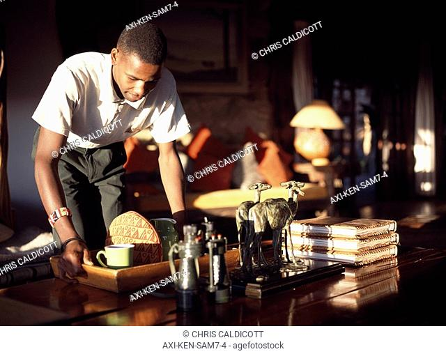 Young man serving tea on tray in home, Kenya