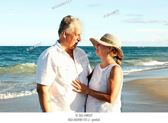 Senior couple on beach, standing face to face