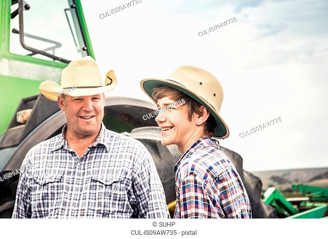 Portrait of farmer and teenage grandson next to farm tractor
