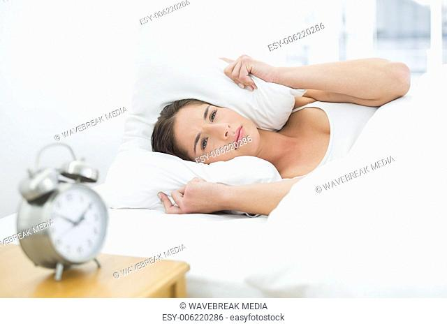 Woman covering ears with pillow and alarm clock on side table