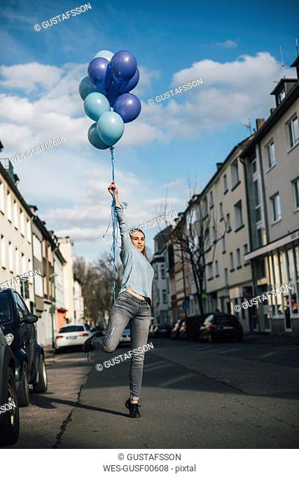Smiling woman with blue balloons on the street