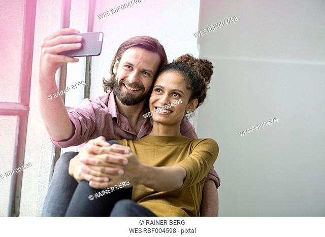 Young couple sitting on window sill taking selfie with smart phone
