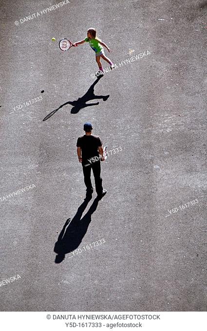 view from above, father learning his little daughter how to play tennis, Geneva, Switzerland