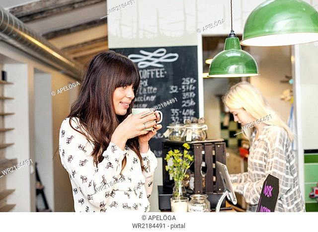 Smiling young woman drinking coffee while owner working at cafe counter
