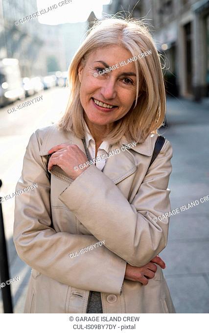 Mature woman on sidewalk in city