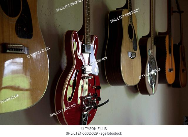 Collection of guitars hanging on wall