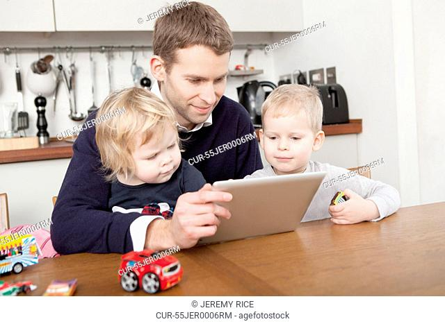Father using digital tablet with son and daughter