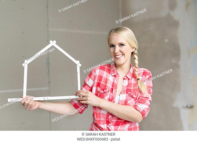 Smiling young woman holding pocket rule in shape of a house on construction site