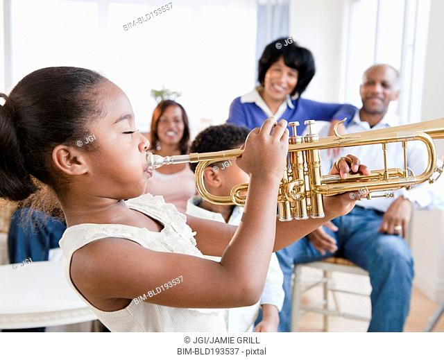 African American family watching daughter play trumpet