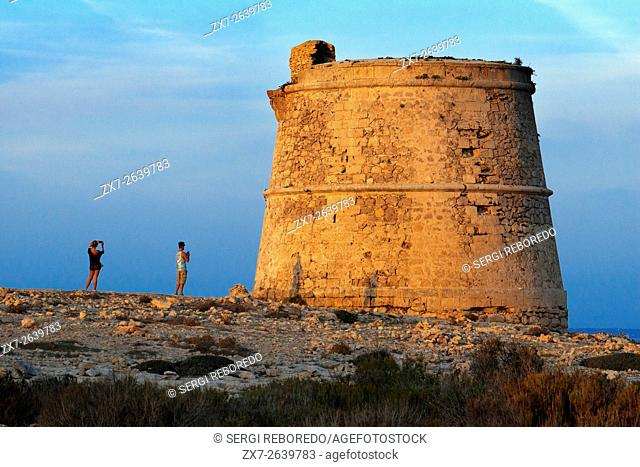 Garroveret Tower on suntet. A couple of tourist taken pictures in Torre des Garroveret - one of the towers on Formentera, Balearic Islands, Spain