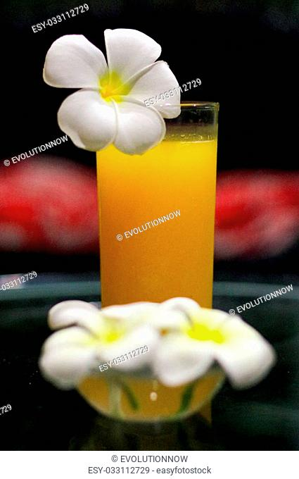 a freshly squeezed fresh orange juice, close-up with a Magnolia blossoms on the glas
