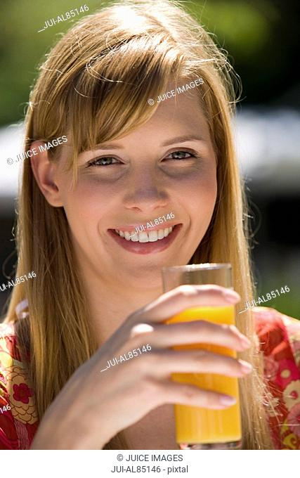 Close up of woman drinking juice outdoors