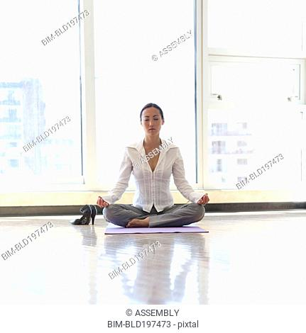 Asian businesswoman practicing yoga on office floor