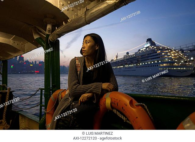 A young woman at the waterfront at sunset with a cruise ship in the background, Kowloon; Hong Kong, China