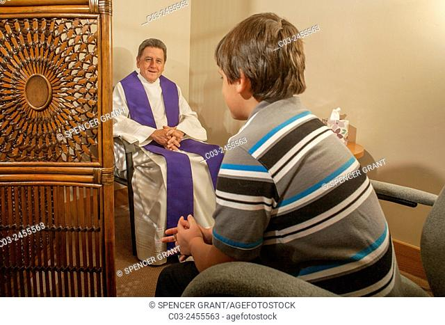 Sitting face to face, a priest hears confession from a boy parishioner at a Laguna Niguel, CA, Catholic church. Note vestments. MODEL RELEASE