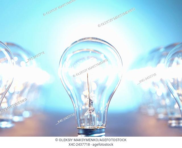 Closeup of lit up incandescent light bulbs on bright blue background. Power consumption concept