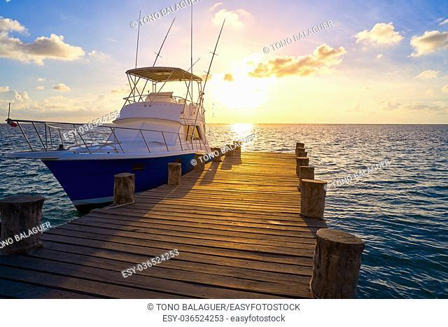 Riviera Maya sunrise fishing boat at beach pier in Mayan Mexico