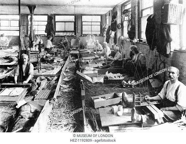 Scott & Sons, 40 Tower Street, London, c1914-1918; showing men weaving chairs