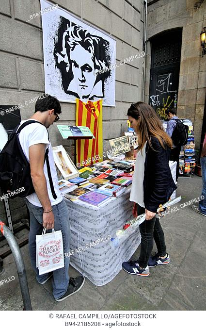 Music Books stall, St George's Day Catalan holiday, Girl with a rose. La Rambla, Barcelona. Catalonia. Spain