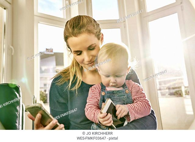 Mother and baby girl holding cell phones