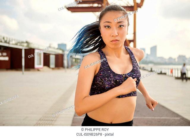 Woman jogging looking at camera, South Bund, Shanghai, China