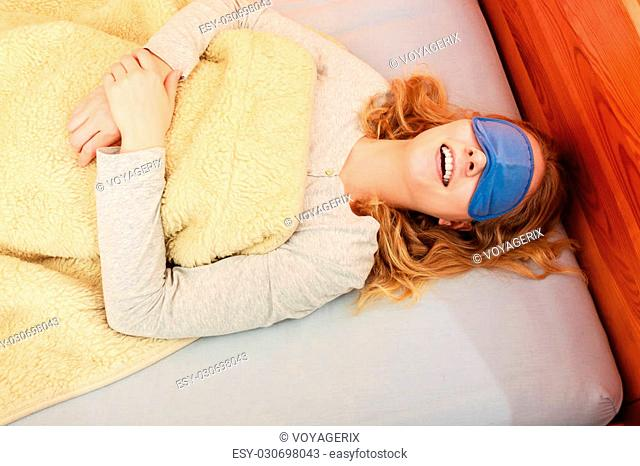 f48eb01656e Tired woman sleeping in bed under blanket wearing blindfold sleep mask. Young  girl taking nap