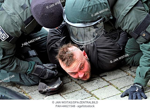 Police officers officers arrest a man during an NPDdemo against an emergency asylum seeker's residence in Leipzig, Germany, 07December 2013