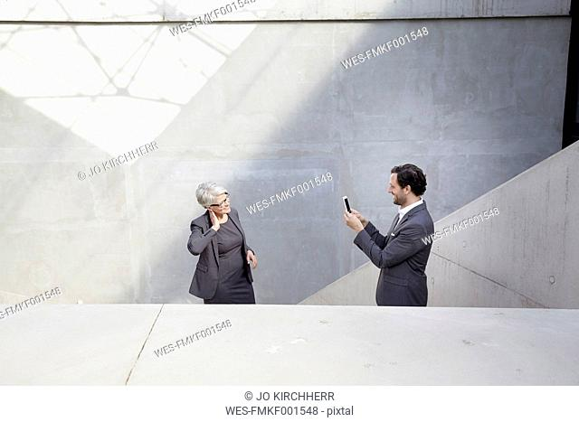 Businessman photographing his female colleague with camera