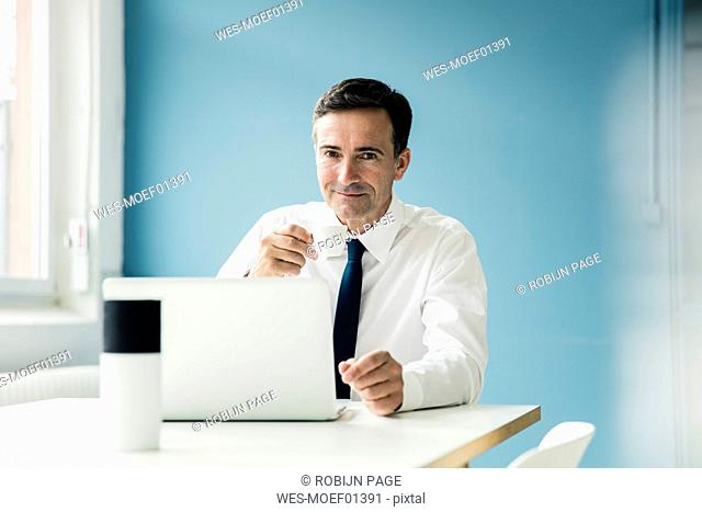 Portrait of confident businessman using laptop on table in office