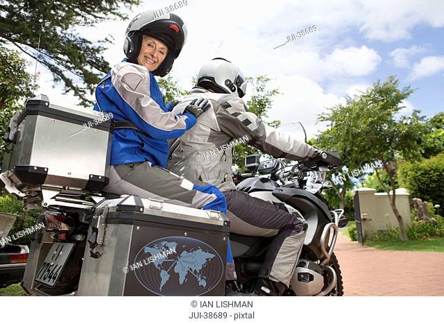 Portrait of happy senior woman wearing helmet on back of motorcycle in driveway