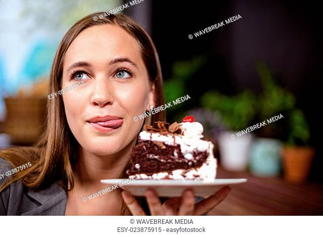 Sweet tooth woman holding piece of cake